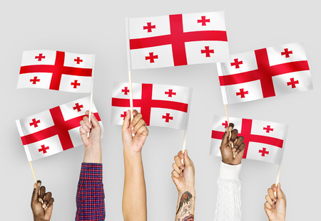 Hands waving flags of Georgia Stock Photo