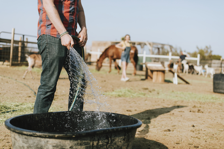 Farmer filling a tub with water Stock Photo