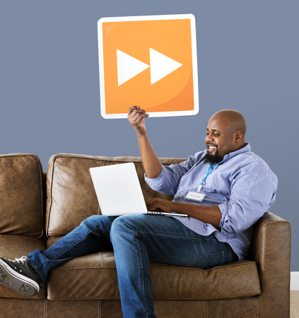 Man using a laptop and holding a fast forward button Stock Photo - 110701459