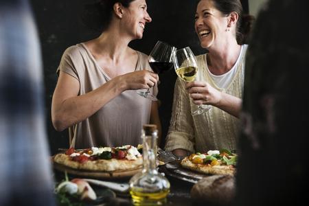 Happy women cheering with glasses of wine