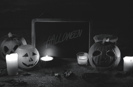 Halloween pumpkins and candles with blackboard