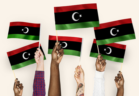 Hands waving flags of Libya 스톡 콘텐츠 - 110909805