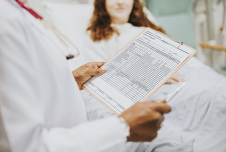 Doctor reading the daily medical report to a patient