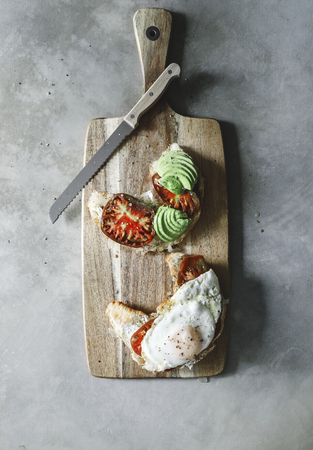 Croissant with heirloom tomato, avocado, and a fried egg Stock Photo