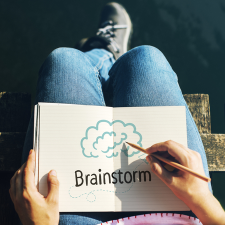 Woman writing Brainstorm on a notebook Imagens