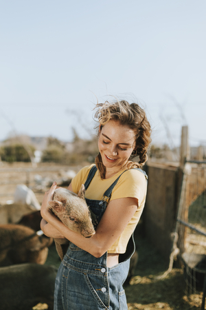 Young volunteer with a piglet, The Sanctuary at Soledad, Mojave Stock Photo