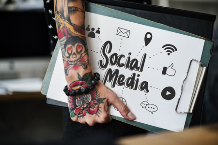 Tattooed hand holding a social media clipboard Banque d'images - 111300103