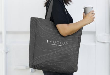 Mujer que lleva una maqueta de bolsa de compras negra