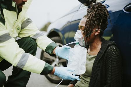 Paramédico masculino poner una máscara de oxígeno a una mujer herida en una carretera Foto de archivo