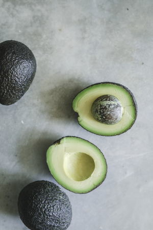 Fresh avocados on a gray background