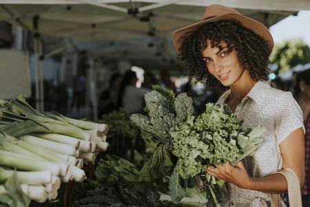 Beautiful woman buying kale at a farmers market