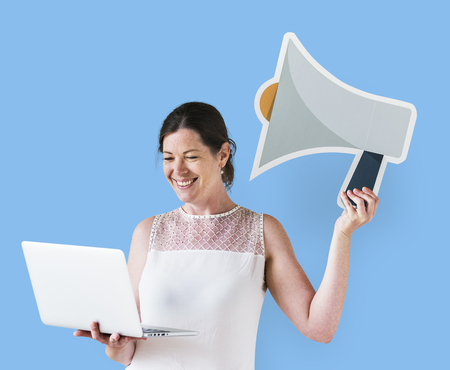 Woman holding a megaphone icon and using a laptop Stok Fotoğraf - 111360120