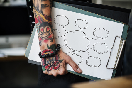Tattooed hand holding an empty cloud clipboard Stock Photo