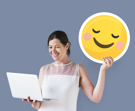 Woman holding a blushing emoticon and using a laptop