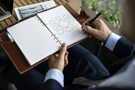 Businessman drawing empty clouds in a notebook