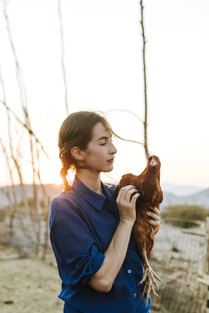 Young woman with a brown hen Imagens