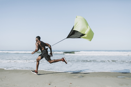 Fit man with a running parachute at the beach Stock Photo