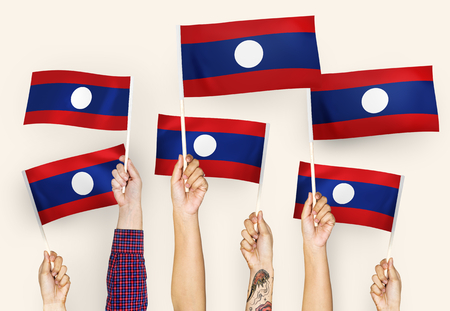 Hands waving flags of Lao PDR Stock Photo