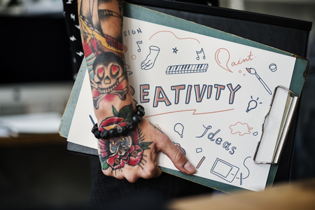 Tattooed hand holding a creativity clipboard