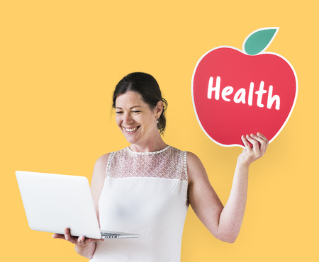 Woman holding a health icon and using a laptop Zdjęcie Seryjne