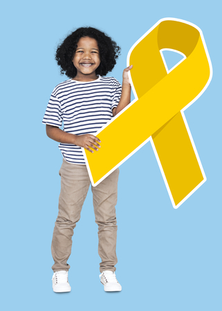 Young boy holding a golden ribbon supporting childhood cancer awareness