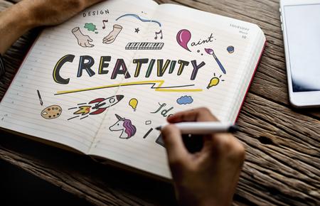 Mann zeichnet Kreativität in einem Notizbuch Standard-Bild
