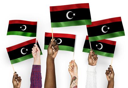 Hands waving flags of Libya