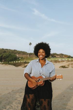 Woman playing the ukulele Stock Photo - 115729434