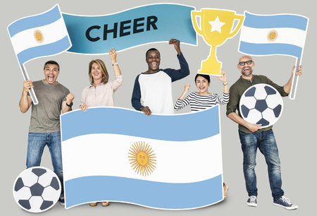 Diverse football fans holding the flag of Argentina 스톡 콘텐츠