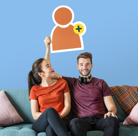 Cheerful couple holding a friend request icon Reklamní fotografie