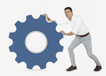 Businessman pushing a blue cogwheel