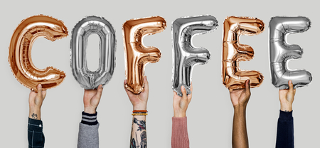 People holding up letters that spell coffee