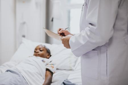 Pediatrician noting down symptoms of a patient