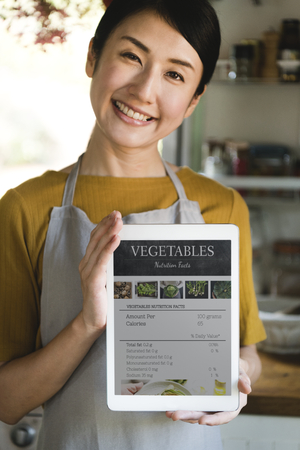 Happy woman holding a tablet with vegetable nutritional facts Reklamní fotografie