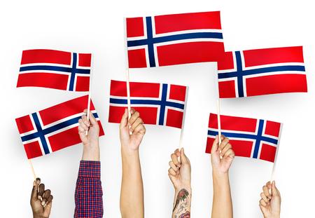 Hands waving flags of Norway