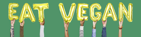 Hands holding Eat Vegan word in balloon letters