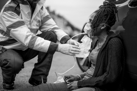 Male paramedic putting on an oxygen mask to an injured woman on a road Фото со стока