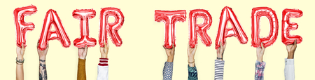 Hände, die Fair-Trade-Wort in Ballonbuchstaben halten