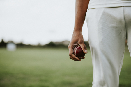 Cricket player holding a leather ball Stockfoto