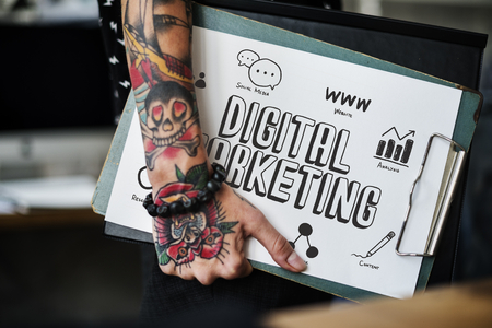 Tattooed hand holding a digital marketing clipboard Banque d'images - 111784148