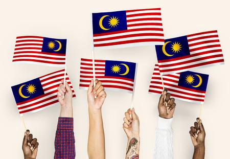 Manos ondeando banderas de Malasia Foto de archivo