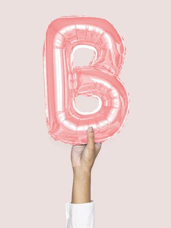 Hand holding balloon letter B 免版税图像