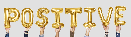 Yellow gold alphabet balloons forming the word positive
