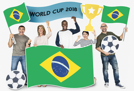 Diverse football fans holding the flag of Brazil