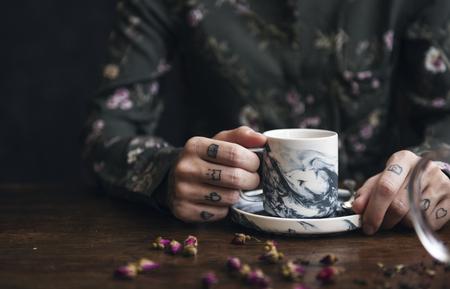 Tattooed woman having a cup of tea Stock Photo