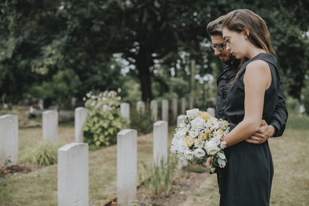 Couple standing together by a gravestone Stock Photo