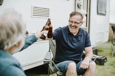 Happy senior men clinking bottle beers 版權商用圖片