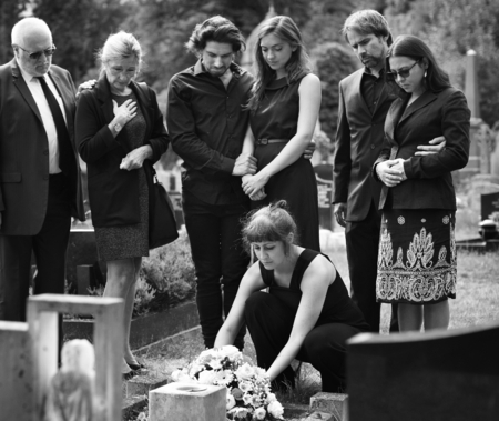 Family laying flowers on the grave Stock Photo - 111840755