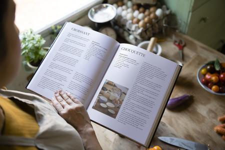 Gelukkige vrouw die een kookboek in de keuken leest