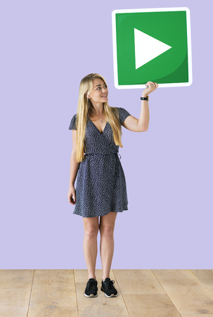 Woman holding a play button icon in a studio